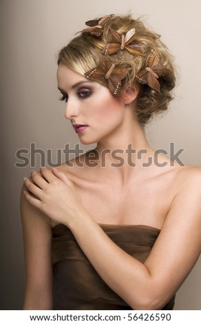 Portrait of young beautiful woman with butterflies in a haird-ress. - stock photo
