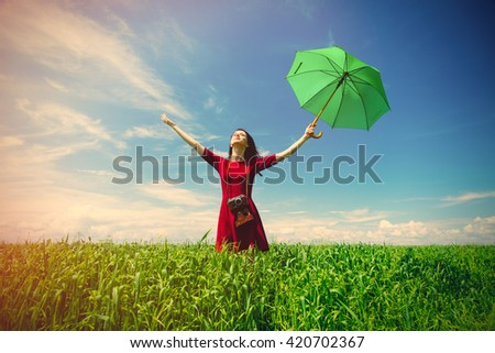 portrait of young beautiful woman with camera and green umbrella in the field