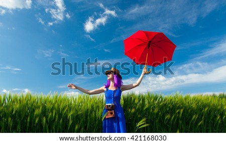 portrait of young beautiful woman with camera and red umbrella in the field