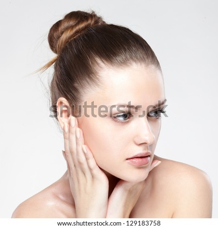 portrait of young beautiful woman with clean skin. On grey background - stock photo