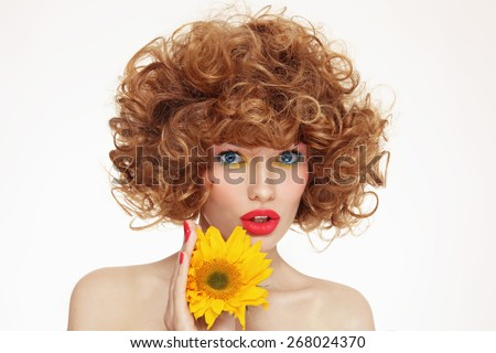 Portrait of young beautiful woman with curly hair and sunflower in her hands - stock photo