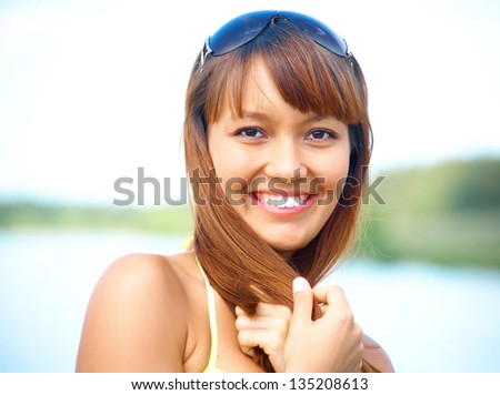 portrait of young beautiful woman with fair hair on background of the  lake