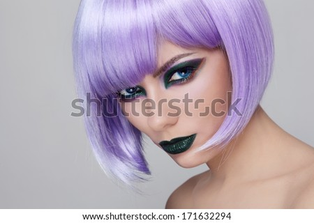 Portrait of young beautiful woman with fancy green make-up and violet wig - stock photo