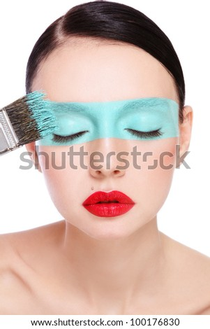 Portrait of young beautiful woman with fancy make-up and paint-brush, over white background