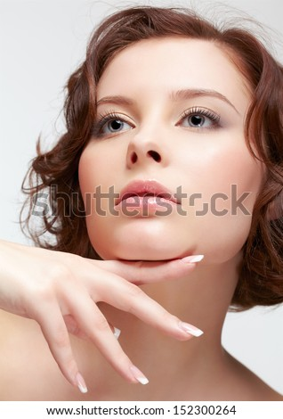portrait of young beautiful woman with french manicure posing with hand below her chin - stock photo