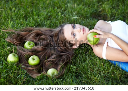 Portrait of young beautiful woman with green apples, outdoors - stock photo