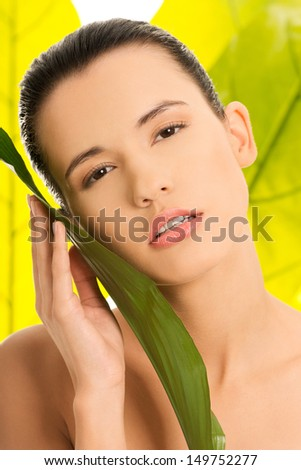 Portrait of young beautiful woman with green leafs in background