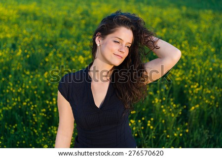 Portrait of young beautiful woman with hand in her hair enjoying sunset over green background and field of yellow flowers . - stock photo