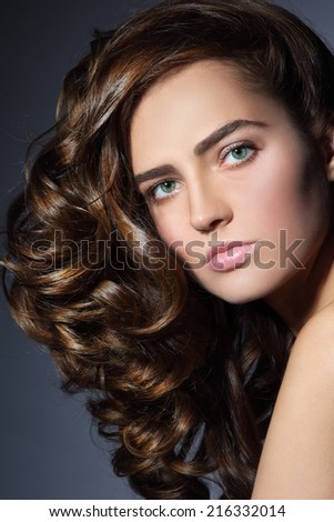 Portrait of young beautiful woman with healthy long curly hair - stock photo