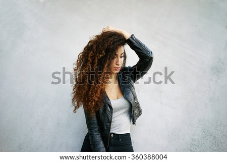 portrait of young beautiful woman with long curly hair wearing a black leather jacket posing on a background of gray concrete wall with copy space area for your text .girl showing her gorgeous hair - stock photo