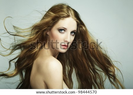 Portrait of young beautiful woman with long flowing hair. Fashion photo