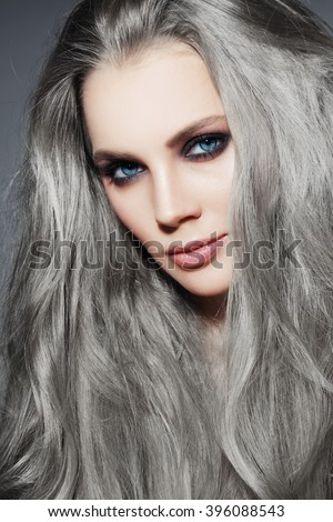 Portrait of young beautiful woman with long grey hair and stylish smoky eyes make-up