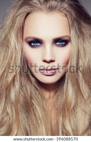 Portrait of young beautiful woman with long hair and smoky eyes make-up - stock photo