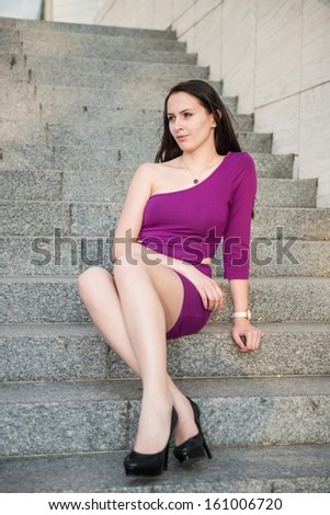 Portrait of young beautiful woman with long legs sitting on stairs with - stock photo