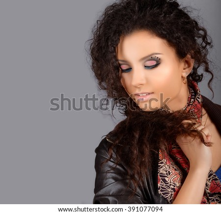 Portrait of young beautiful woman with makeup. Dark background. Wearing earrings.