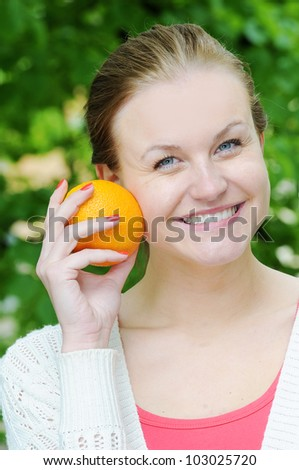 Portrait of young beautiful woman with orange - stock photo