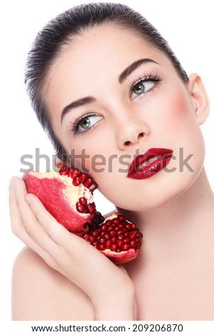 Portrait of young beautiful woman with pomegranates in her hand over white background - stock photo