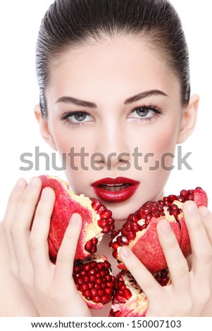Portrait of young beautiful woman with pomegranates in her hands, over white background