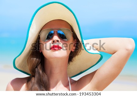 portrait of young beautiful woman with red lips and hibiscus in straw hat - stock photo