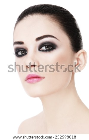 Portrait of young beautiful woman with smokey eyes over white background - stock photo