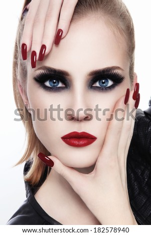 Portrait of young beautiful woman with smoky eyes and long nails over white background - stock photo