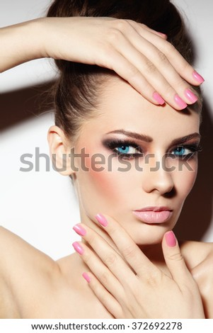 Portrait of young beautiful woman with smoky eyes touching her head