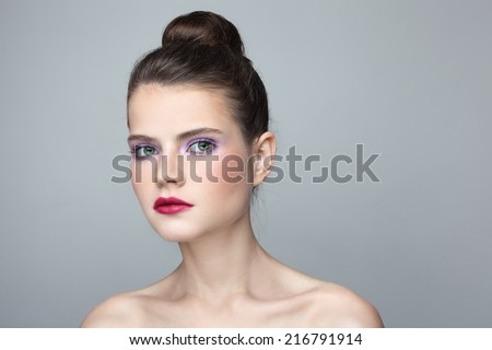 Portrait of young beautiful woman with stylish make-up and hair bun - stock photo