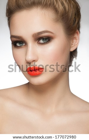 Portrait of young beautiful woman with stylish makeup with orange lipstick - stock photo