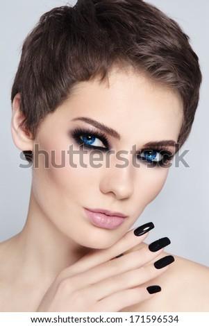Portrait of young beautiful woman with stylish short haircut and smokey eyes - stock photo