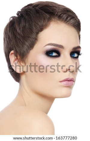 Portrait of young beautiful woman with stylish short haircut and smokey eyes over white background - stock photo