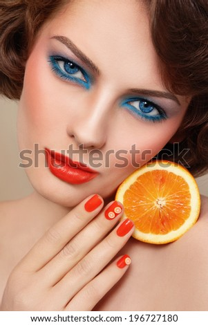 Portrait of young beautiful woman with trendy turquoise and orange make-up