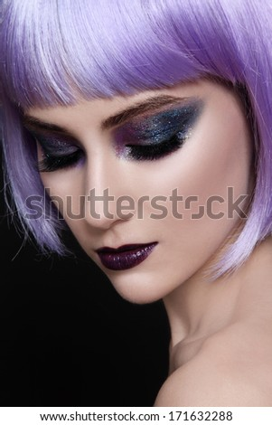 Portrait of young beautiful woman with violet wig and sparkly make-up