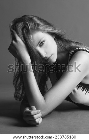 Portrait of young beauty blond woman looking at the camera, touching her hair, black and white, grey background.