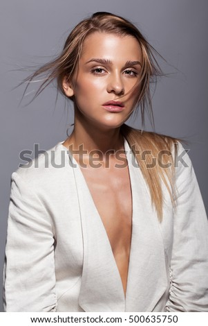 Portrait of young beauty woman in casual white jacket on gray background