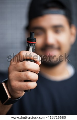Portrait of young black man holding electronic vaporizer, wearing smart wrist watches.Modern gadget that lets you always stay connected to internet,social media, focus on trendy e-cigarette device - stock photo