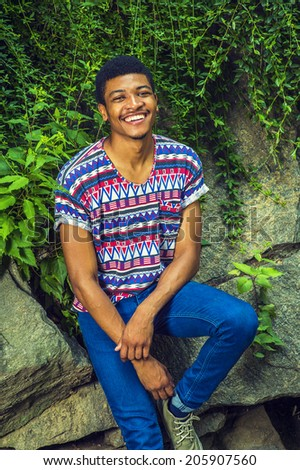 Portrait of Young Black Man. Wearing a short sleeve, collarless, colorful pattern shirt, a young handsome guy is sitting against rocks with green leaves, smiling, charmingly looking at you.  - stock photo