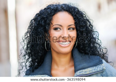 Portrait of young black woman smiling with braces  - stock photo