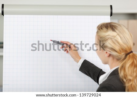 Portrait of young blond businesswoman writing at flip chart in office - stock photo