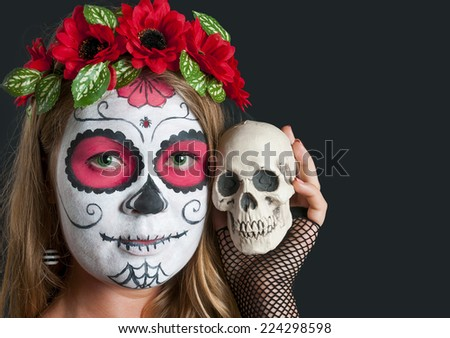 Portrait of young blond girl in black dress with Calavera Mexicana makeup mask and with skull in her hand. Halloween  - stock photo