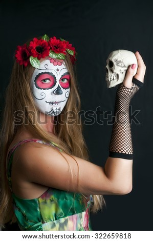 Portrait of young blond girl in colorful dress with Calavera Mexicana makeup mask and with scull in her hand - stock photo