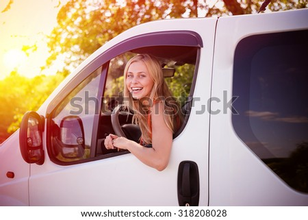 Portrait of young blond girl laughing driving white car. Beautiful woman looking from car window on sunset backround. - stock photo