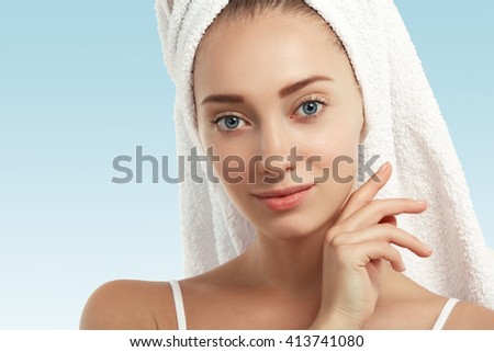 Portrait of young blond girl with fresh and clean skin, wearing white bath towel on her head, touching her face, looking with cute smile at the camera, against blank wall with copy space for your text - stock photo