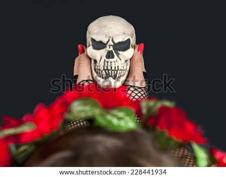 Portrait of young blond girl with scull in her hand - stock photo