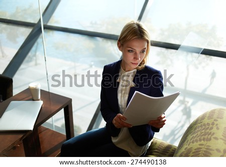 Portrait of young blond hair business woman reading documents in bight light office interior sitting next to the window, attractive business woman read some documents before meeting - stock photo