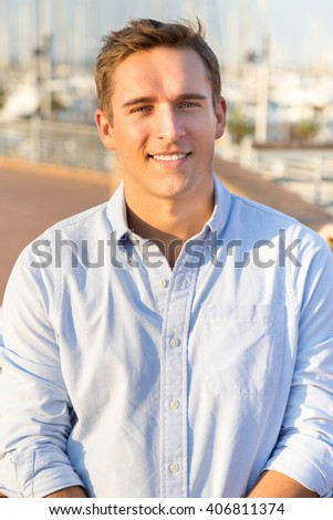 Portrait of young blond man wearing casual shirt against port background. Close up of young guy in business clothes with warm yellow color tones. Genuine smiling person looking in camera.  - stock photo