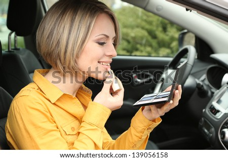 Portrait of young blond woman applying makeup while in the car