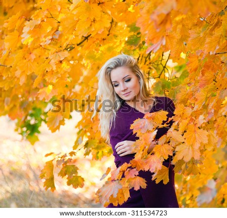 Portrait of young blond woman in autumn color