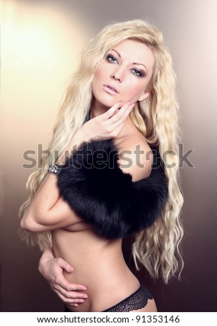 portrait of young blond woman in fur and lingerie - stock photo