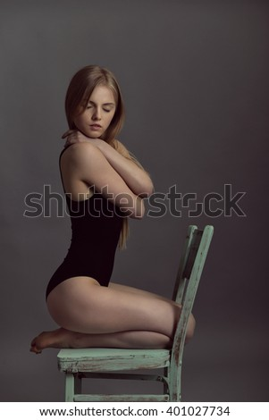 Portrait of young blond woman posing in studio with retro obsolete chair over gray background.