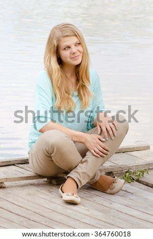 Portrait of young blonde girl by the riverside.